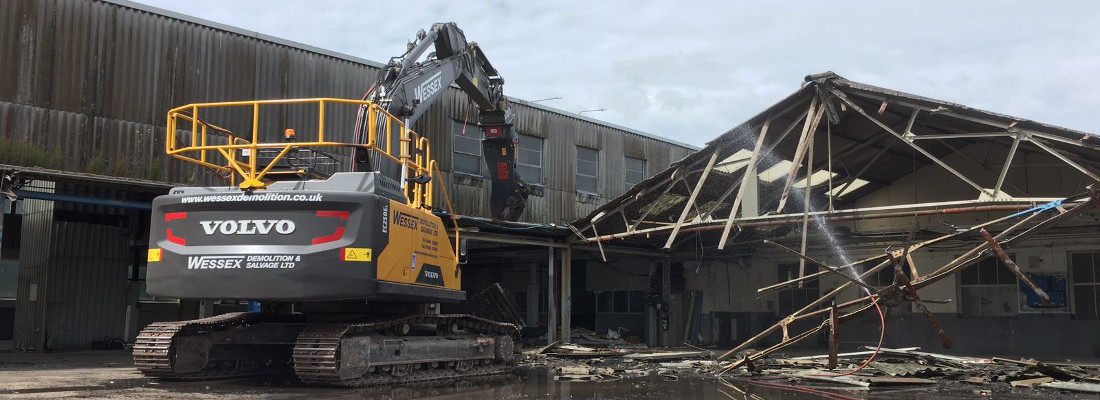 Volvo EC250EL Excavator removing a metal sheet roof