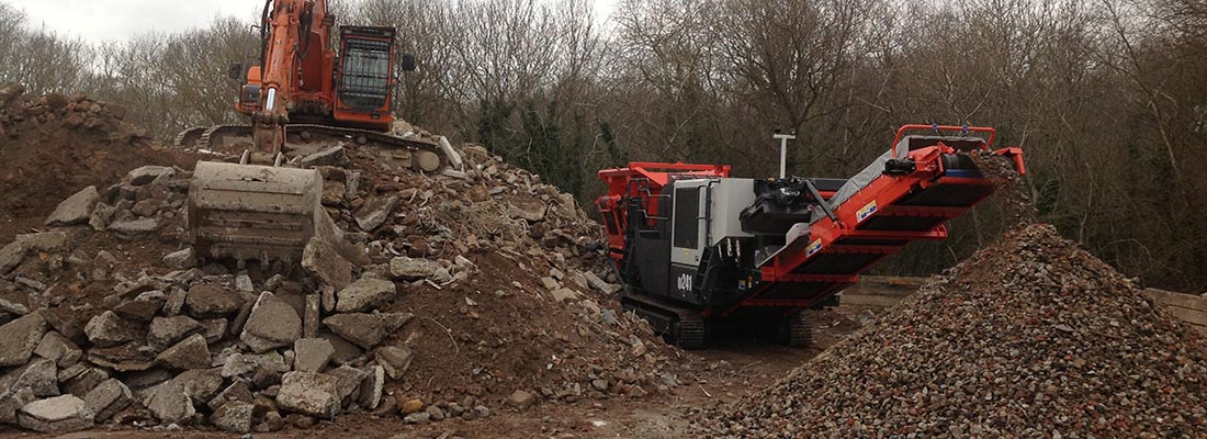 Excavator and Crusher in operation at the aggregates yard, Southampton